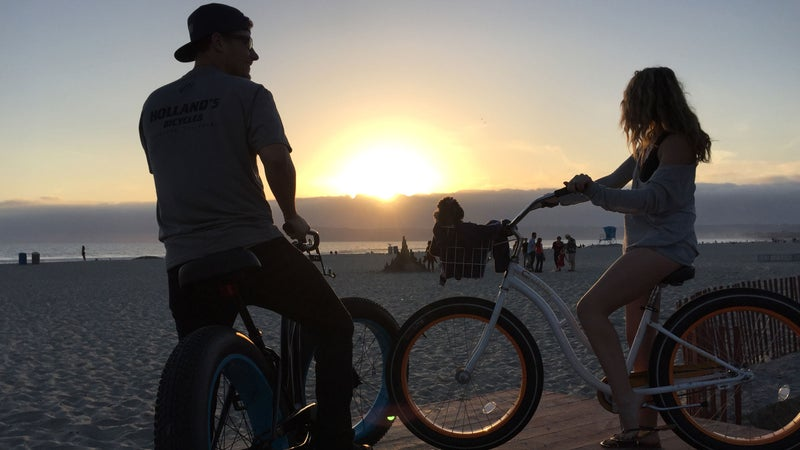 A man and woman take in the sunset after fat biking on Coronado Beach.