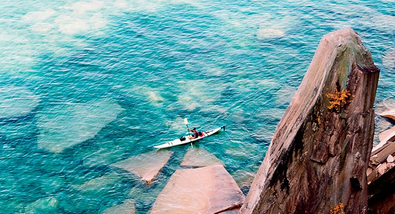 A sea kayaker passes sail rock in Pictured Rocks National Lakeshore.
