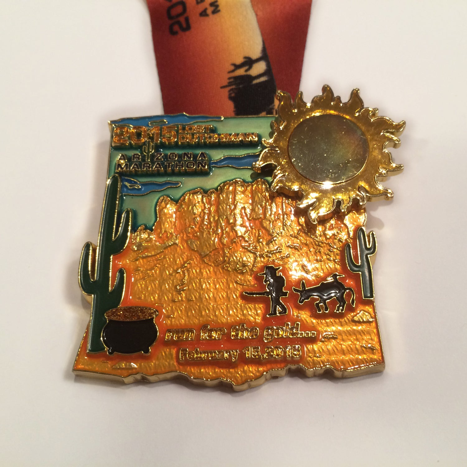 Solera: It's fitting that a race that runs through the burnt reds and oranges of the southwestern desert under a perfect blue sky should have a colorful medal. Organizers ditched their usual subdued approach and went for a full explosion of color. As a novelty bonus, the sun's heat rays rotate.