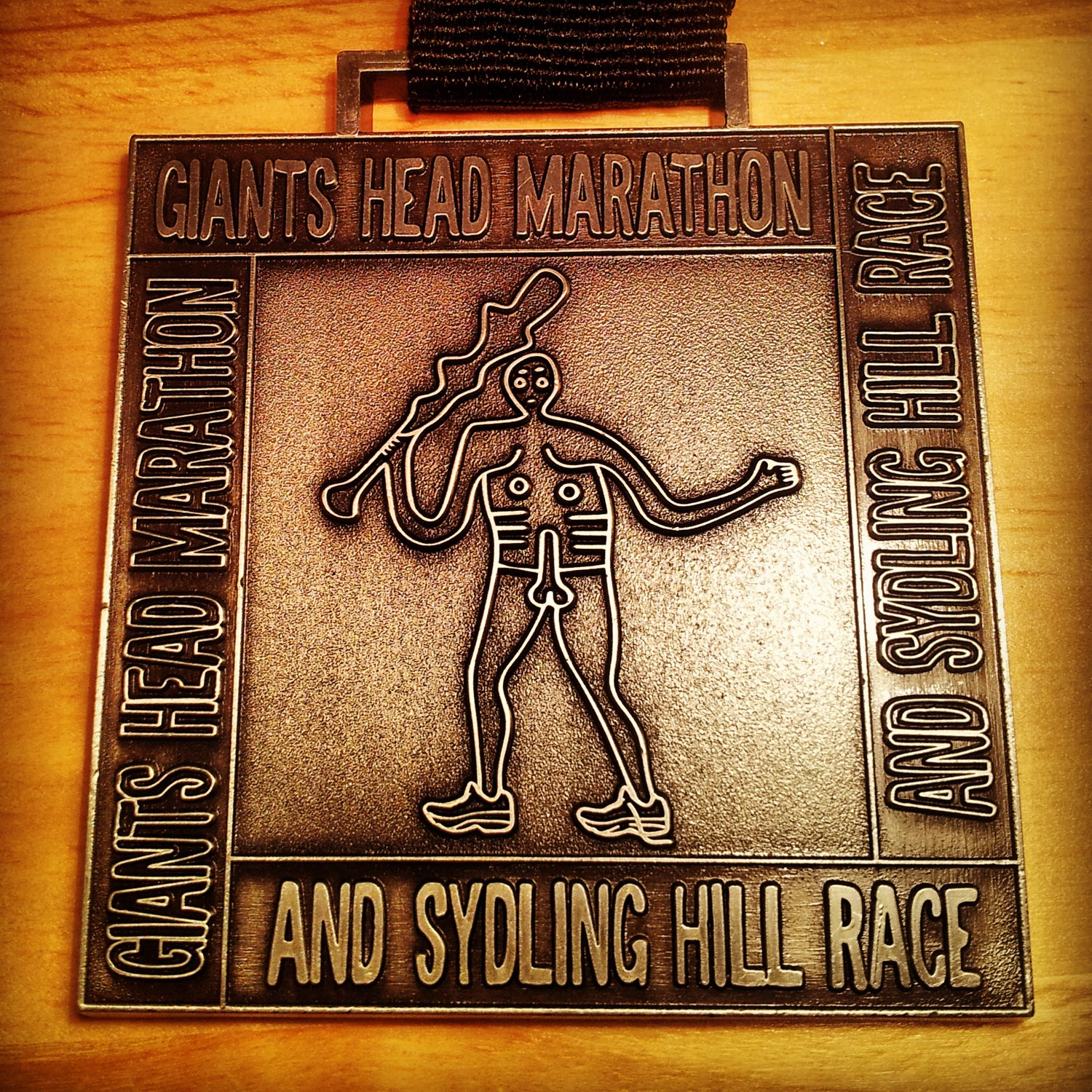 """Williams: Speaking of male genitalia, the next medal was fabulous enough to make me sign up for the (slightly long) marathon despite it's hellish elevation profile. The Giant's Head Marathon, in Dorset, takes place in the beautiful English countryside, including the historical Cerne Abbas Giant, a giant chalk drawing on a hillside. The Cerne Abbas Giant features prominently on the medal, including his prominent member. It's also a weighty piece of hardware and a challenging day out. Bonus: At (roughly) 20 miles, there is a """"Love Station,"""" which features tray bakes, cake, sandwiches, cider, and flavored vodka.Fun fact: The weekend was so filled with innuendo that I genuinely asked for the """"spicy penis sauce"""" instead of the spicy peanut sauce the following day in a restaurant."""