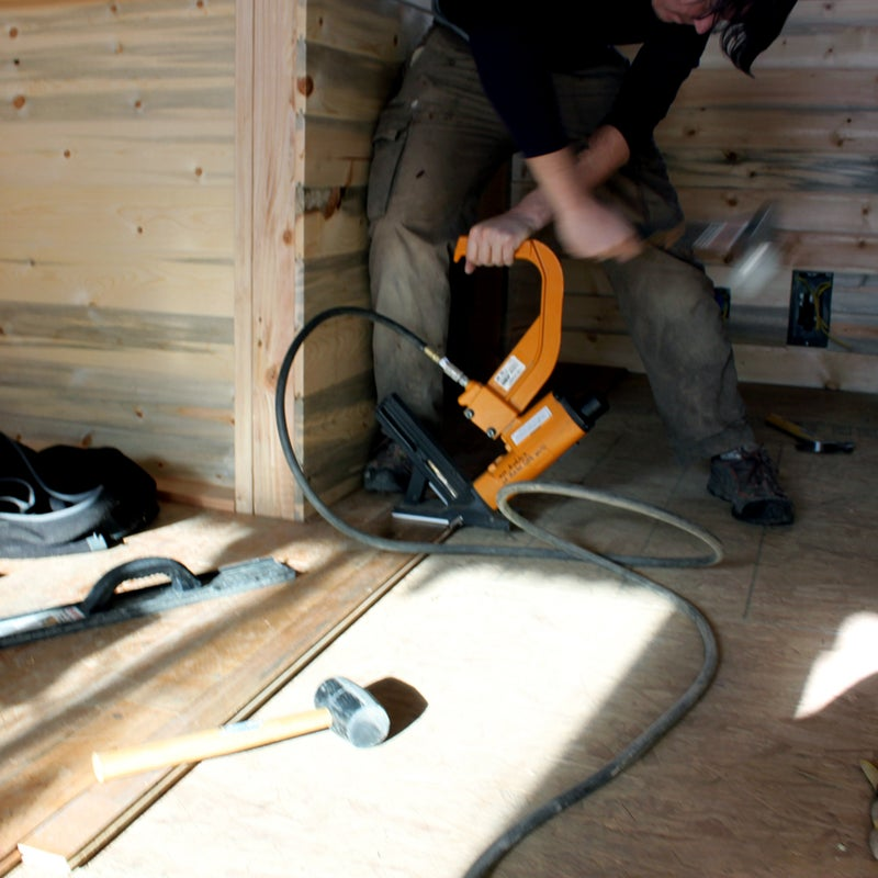 """At the start of the project, the couple planned to purchase only the essential tools. But they """"quickly learned that buying tools and always having them on site ends up saving you tons of money and time,"""" says Smith. It's good to have at least one spare hammer, screwdriver, and electric drill nearby. Here, Christopher manhandles a flooring stapler, a specialized tool they rented for a few days."""