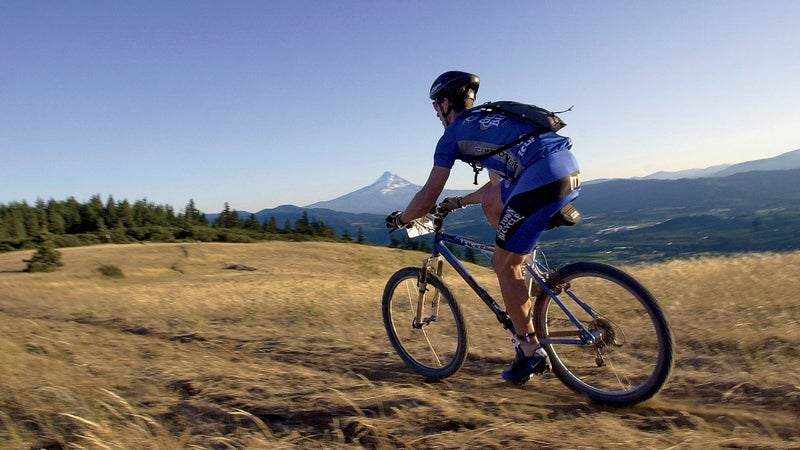20 Jul 2002, Hood River, Oregon, United States --- A rider races down the trail just before sunset in the 24 hour mountain bike marathon during the Gorge Games. --- Image by © Tony Wayrynen/NewSport/Corbis