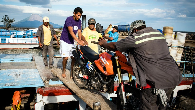 Workers unload the author's motorcycle from a ferry at the port city of San Jorge, on the shores of Lake Nicaragua.