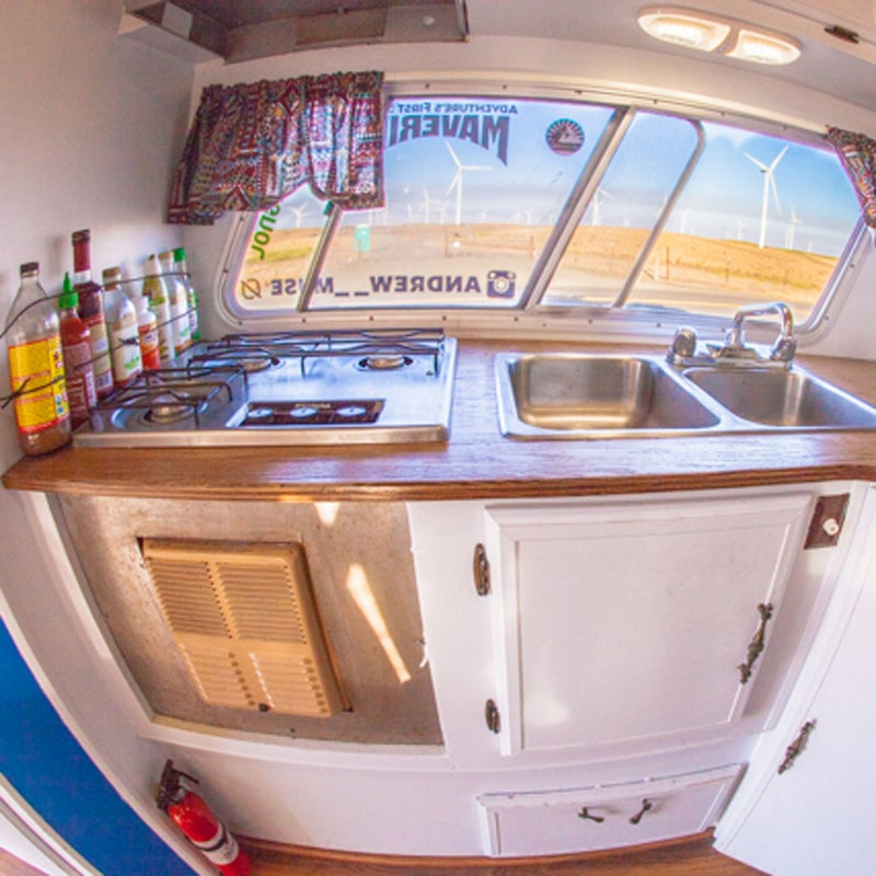 The camper came with a three-burner stove and sink, which makes life easy. The stove even doubles as a heater on extremely cold nights. I replaced the old dilapidated countertop with a piece of sanded oak that I stained. Cheap, easy, and looks great.