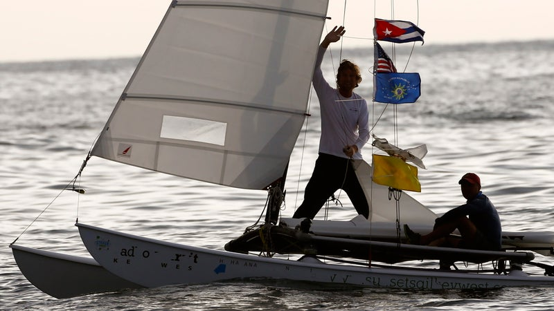 Second-place sailor Seth Salzmann waves alongside teammate Wade Miller on their catamaran decorated with Cuban and U.S. flags as they arrive from Key West, Florida, to the Marina Hemingway.