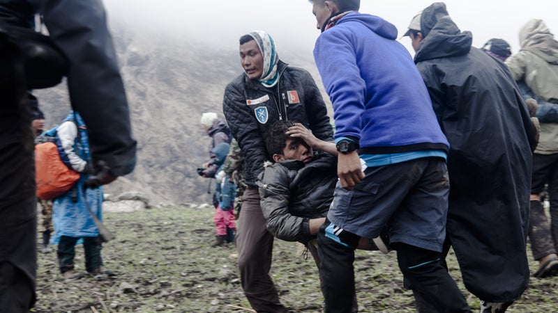 A group of Nepalese survivors rush their seriously injured friend to a waiting helicopter, hoping to get him one of the limited seats out of the valley on the day after the earthquake. Sunday, April 26, 2015.