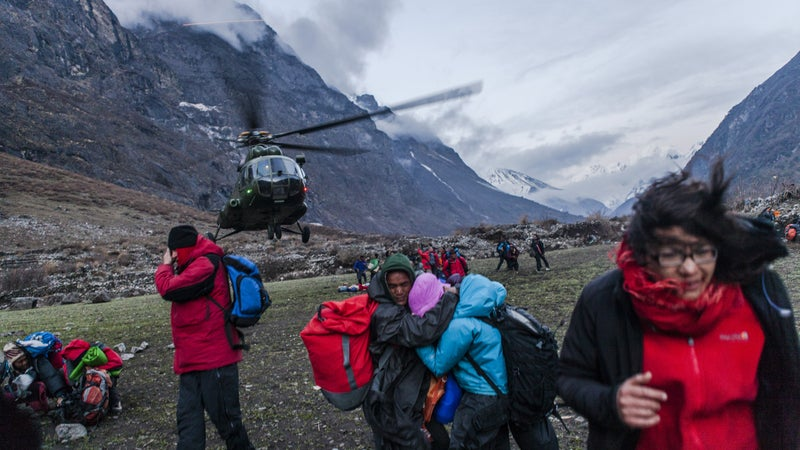 A group of survivors shield themselves against the powerful wind from a departing Nepalese Army helicopter.Monday, April 27, 2015.