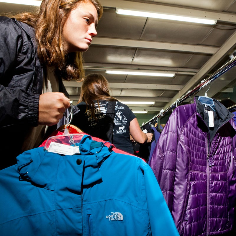 A shopper nabs a shell from The North Face and a puffy from REI, both for $35.99.