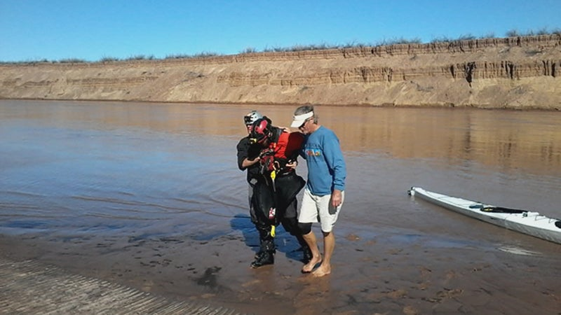 Ben Orkin is helped to the riverbank after his epic paddle.
