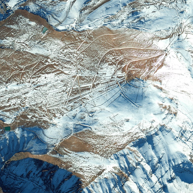 This May 2013 image shows the cat track winding around the conical slopes of Chile's El Colorado, the closest ski area to Santiago (about a one-hour drive). El Colorado slopes lie between two other Andean resorts, La Parva (visible on the photo's upper margin) and Valle Nevado. The three are interconnected by a series of lifts and, all told, comprise the Tres Valles ski area, with 7,000 skiable acres, 40 chairlifts, and four base villages.