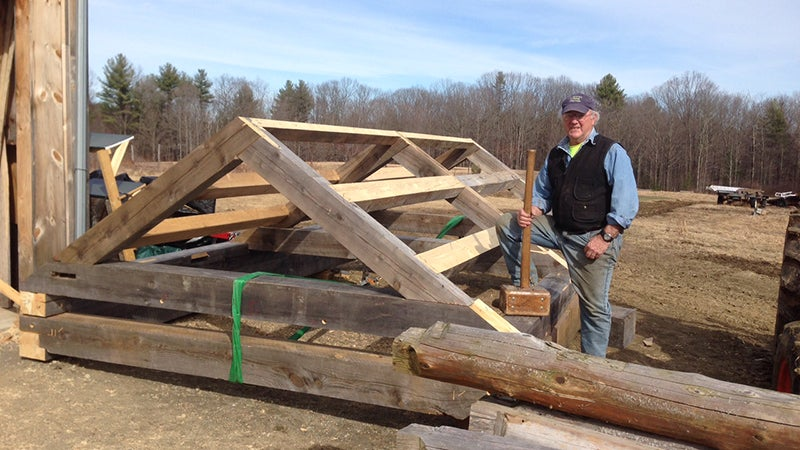 Elwell stands beside the cabin's roof frame, outside his workshop in Ashfield, Massachusetts.