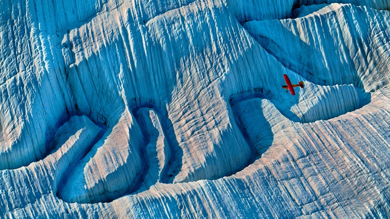 A bush plane flies over a glacier deep in Wrangell–St. Elias