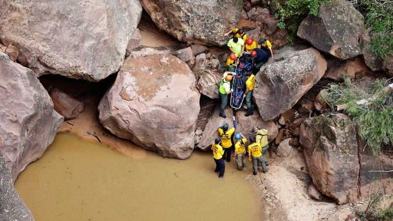 Rescuers pull a body from Pine Creek after the flash floods.