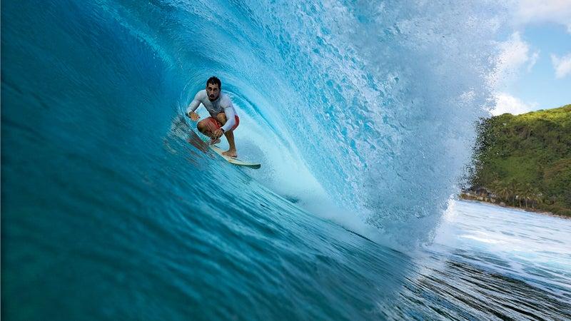 Jameson Kaeo Newtson, a local surfer, riding a wave off the western coast of Tutuila.