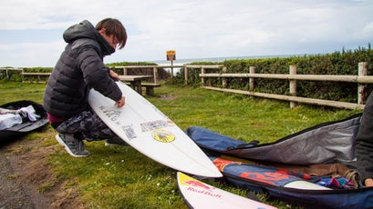 Jamie's buddy Kaikea Elias waxing his board before heading into the choppy and chilly Pacific ocean.