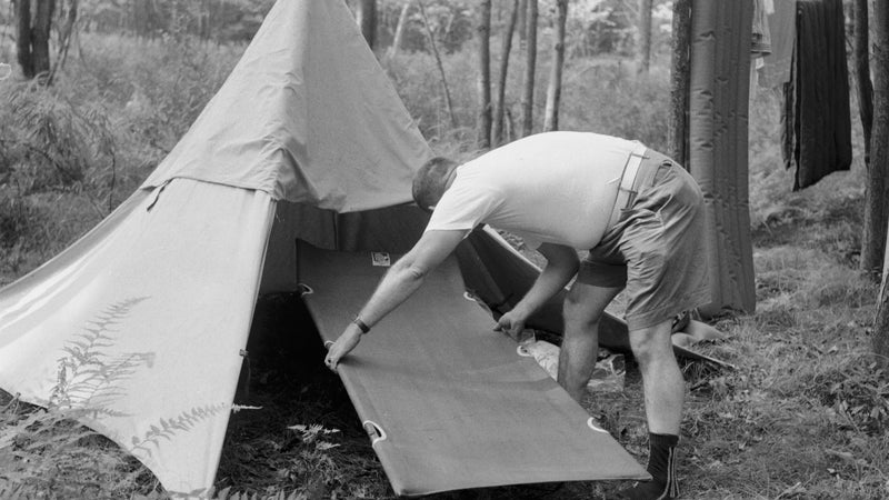circa 1955:  With his tent set up for an adventure holiday, a camper realises that his camp bed is too large for the tent.  (Photo by Jacobsen /Three Lions/Getty Images)