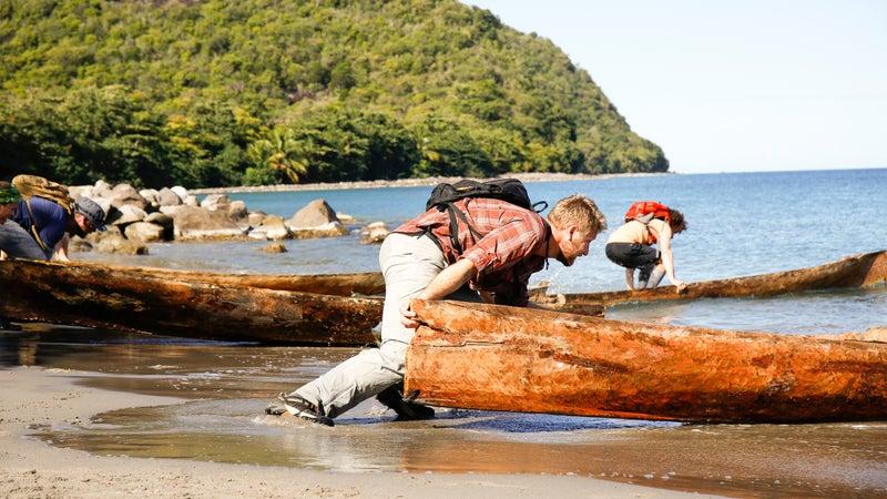 Derek pushing his canoe into the water.