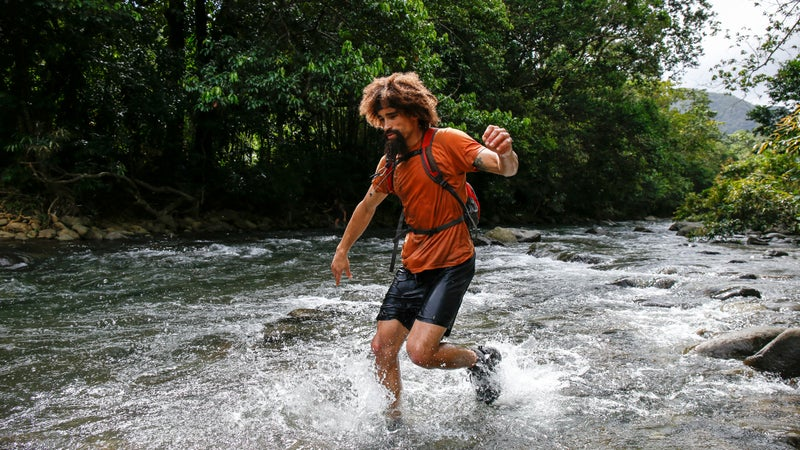 Jeremy running through the edge of the large river.