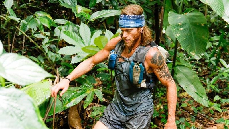 Tim Olson walking through a creek.