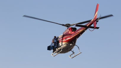 Rex holds on to the helicopter as it takes him up to 10,000 feet for his first flight