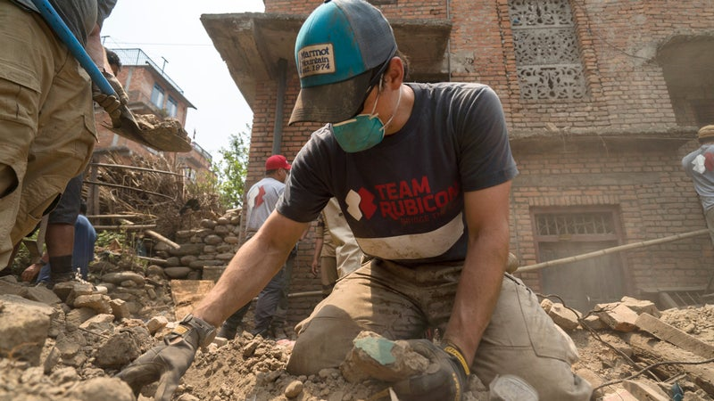 Team Rubicon member Tim Fortney looks for valuables lost underneath the rubble.