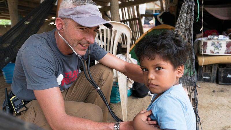 Team Rubicon member Scott Seager listens closely to the breathing of an Ecuadorian child in Bahia, Ecuador.