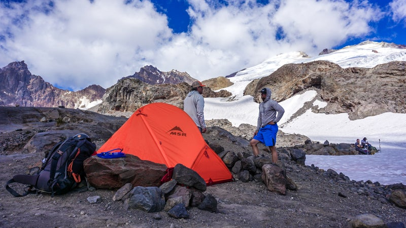 Matt and Ryan from BC Adventure Guides stand outside the Access 2 they shared. With ample stone stacking supporting ice axes and pickets tied to guy lines, they managed to keep their tent in decent shape throughout the wind storm. Others didn't fair so well.