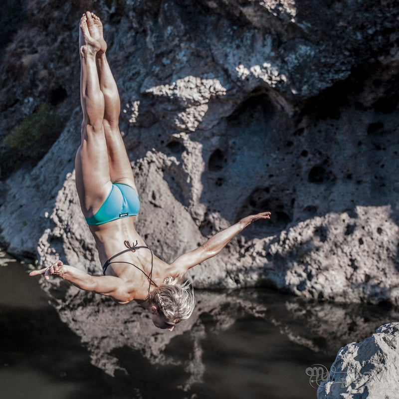 Jessie dives backwards off a rock, during her first attempt at a new rock pool.
