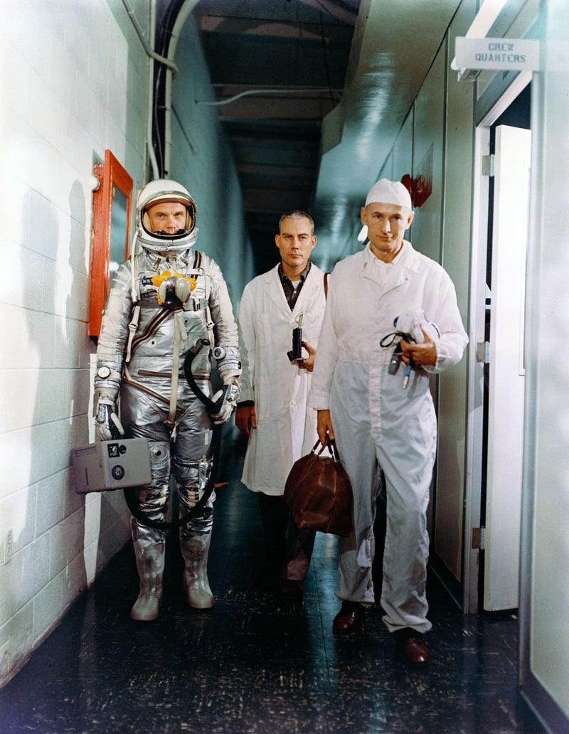 Astronaut John H. Glenn Jr. (left), Dr. William Douglas, astronauts flight surgeon, and equipment specialist Joe Schmitt leave crew quarters prior to Mercury-Atlas 6 (MA-6) mission. Glenn is in his pressure suit and is carrying the portable ventilation unit.
