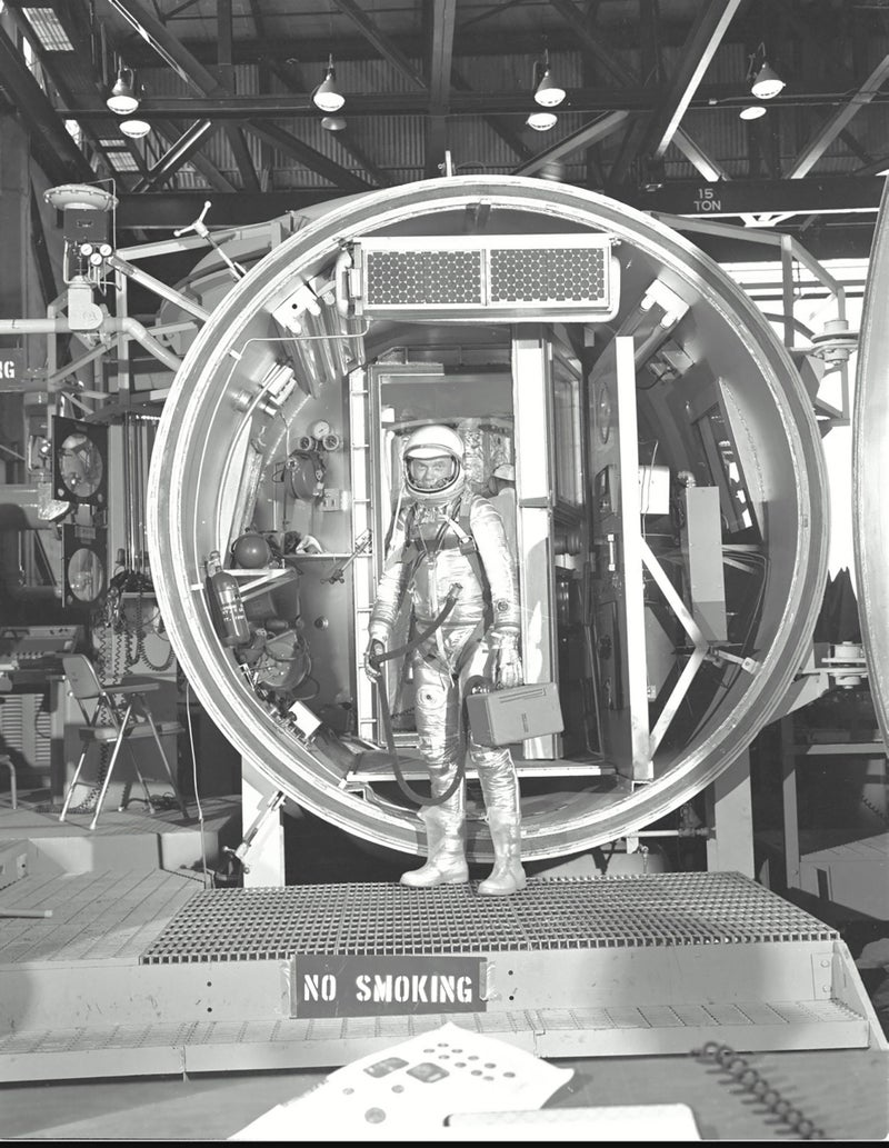 Astronaut John H. Glenn Jr., suited with hose to suit ventilation unit attached, during altitude chamber test. He is standing in the entrance to the test chamber with his helmet visor down.