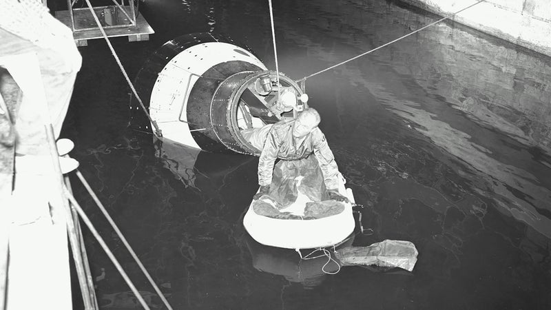 Astronaut John H. Glenn Jr., pilot of the Mercury Atlas 6 spaceflight, emerges from an egress trainer during training activity at the Langley Research Center. He is attempting to transfer onto a life raft from the mock-up of the Mercury capsule.