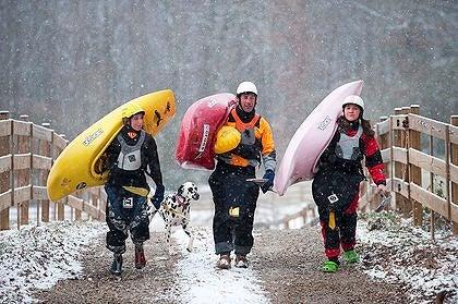 Dane, Eric and Emily Jackson shoulder their kayaks as their dog, Roxy, follows close behind near their home in Rock Island, TN.