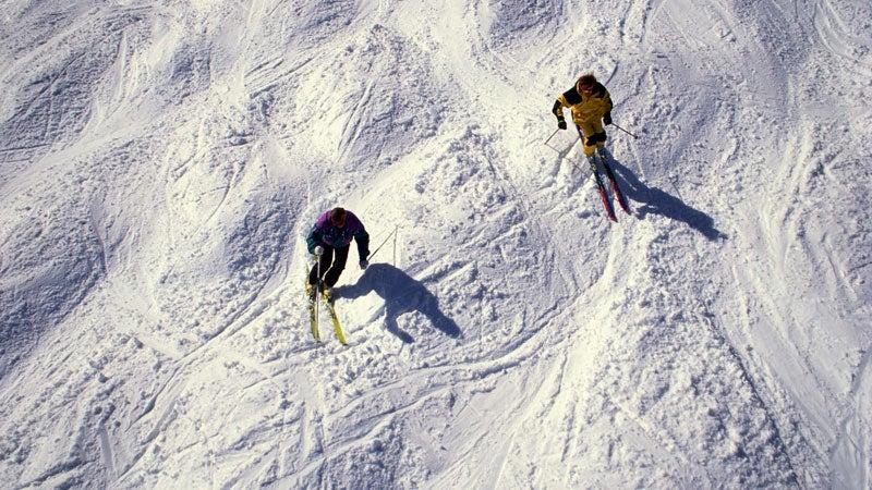 Two men skiing bumps