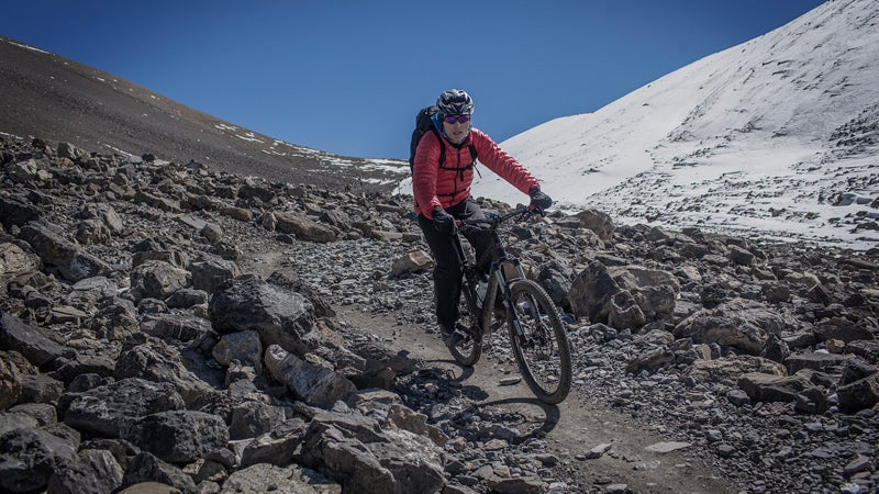 October 22, 2013 - Annapurna, Nepal - After crossing the 5,416m Thorung La Pass on the Annapurna Circuit, a group of mountain bikers rode along a narrow path through rock scree down the mountain towards the town of Muktinath and the historic Kali Gandaki Valley.