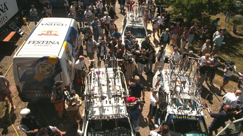 Journalists, riders, and support staff gather around the Festina vehicles involved in the team doping scandal.