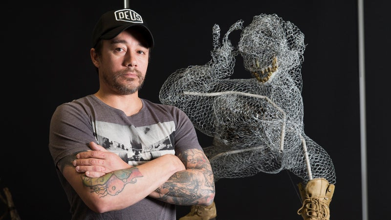 Lance Corporal Ty Tranter, a soldier in the Australian Army, stands proudly in front of his sculpture for the ADF's Arts for Recovery, Resilience, Teamwork, and Skills program showcase at the University of Canberra.