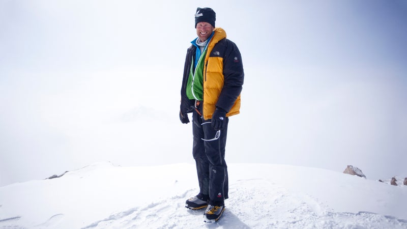 Climber Conrad Anker stands for a portrait on a snow mound with a white background.