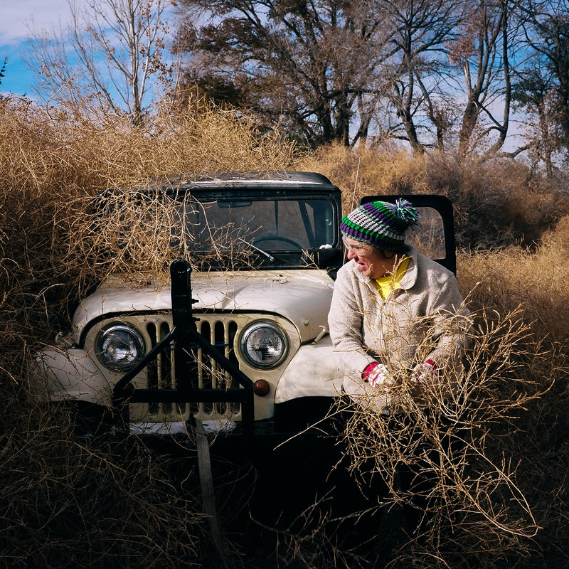 Patty Neher removing tumbleweeds from her yard and jeep. Hanover, Colorado.