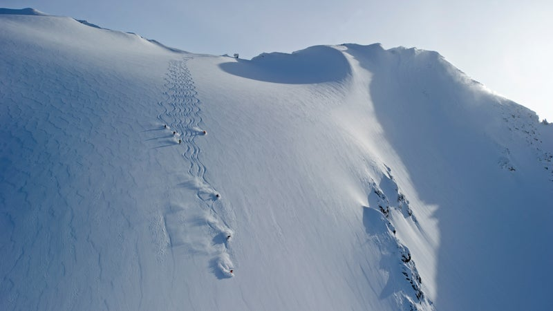 A group of heliskiers at CMH Cariboos snake their way down a drool-worthy open powder slope.