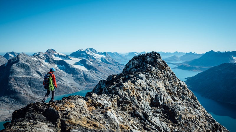Andrew summits a peak with Tasiilaq Fjord in the distance. Has anyone been up here before? Has anyone taken this route to the top? It's impossible to know for sure.