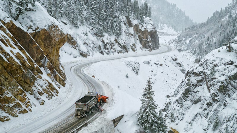 A snowplow pushes snow off the edge as it makes it's way through the canyon.
