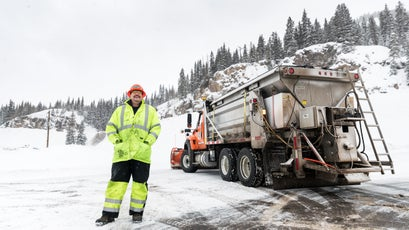 Klein stands by as workers trigger avalanches above the road.