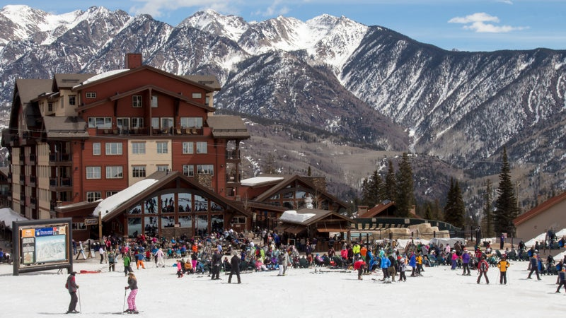 A crowd of skiers and snowboarders hang out at the base area of Purgatory ski resort in Durango, Colorado.