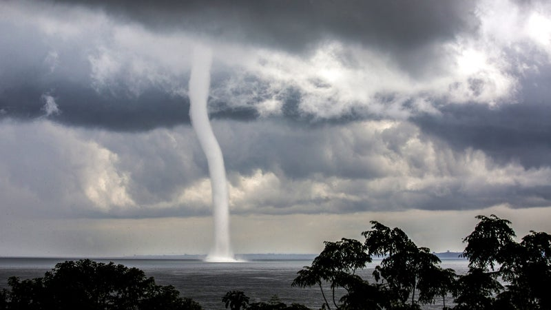 A waterspout is photographed over Lake Victoria, Uganda. Thousands of small birds can be seen flying around at its base.
