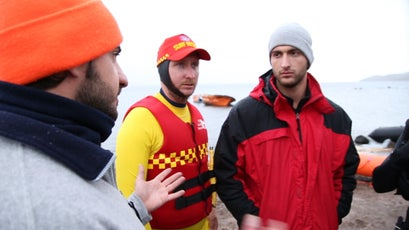 Lifeguards prepare for a large boat of refugees coming to shore.