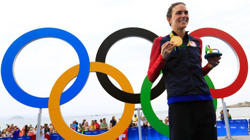 epa05502516 Gwen Jorgensen of the USA poses with her gold medal in front of the Olympic Rings after winning the women's Triathlon race of the Rio 2016 Olympic Games at Fort Copacabana in Rio de Janeiro, Brazil, 20 August 2016.  EPA/HOW HWEE YOUNG