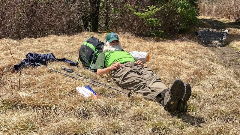Sanders rests alongside the trail.