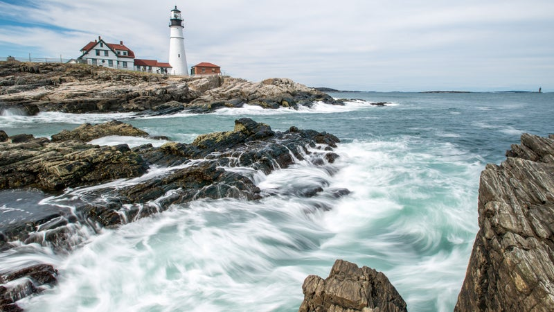 The famous lighthouse at Portland Head rests confidently above the crashing surf in Cape Elizabeth, Maine.