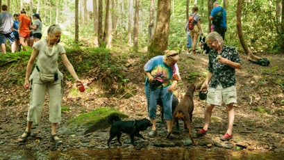 Masja Ott, left, Doris Newton, middle, and David Newton, right, take a moment to let their dogs play in Copperas Creek.