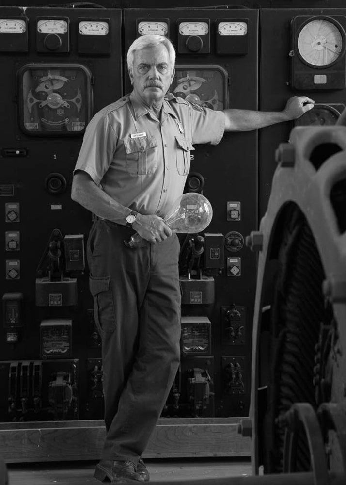 Jim stands in front of a generator instrument panel. Formerly used in Yellowstone National Park, the generator was powered by the energy of falling water through domestic water piping to supplement electricity production for the local utility company.